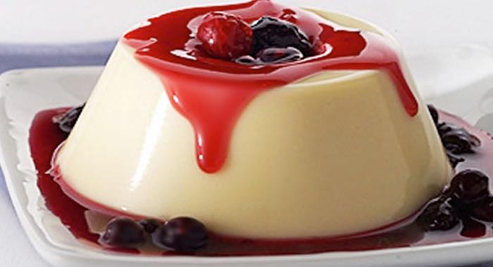 Flan de queso bañado en salsa de frutos rojos.
